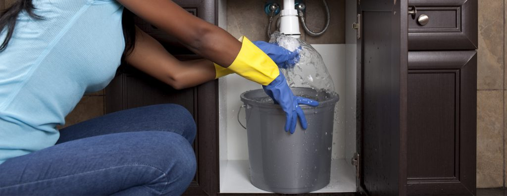 woman wearing rubber gloves with a bucket below a sink that's leaking water.