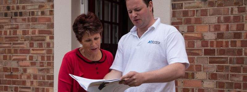 Plumbing Engineer with a client reading a brochure outside the front door.