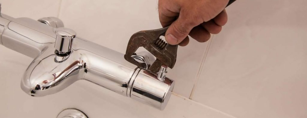 Plumbing Engineer with spanners tightens a bath tap.